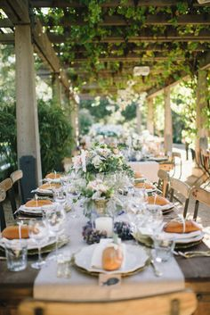 Covered in vines — a fantastic outdoor tablescape.