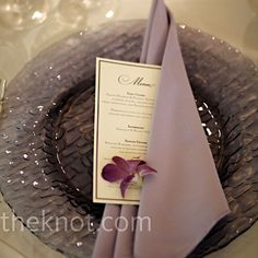 Crisp white linens set the canvas for the translucent, lavender dinnerware. The menus were tucked inside pale purple napkins and adorned with orchid blooms.