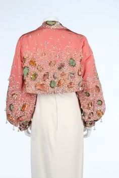 Schiaparelli couture and Lesage embroidered salmon-pink faille bolero jacket, c 1948 heavily embellished with pearlised sequins, appliqued with puckered ombre velvet amoeba-shaped motifs with radiating gilt tinsel strip aureolas, and dotted with iridescent celluloid bell-shaped pendants studded with crystals, the jacket with wide collar, slightly flared hem, full sleeves caught into cuffs, each with prestuds to adjust the opening on the inside, lined in salmon-pink silk
