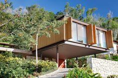 No cruzamento entre os dois volumes que setorizam e distribuem o programa desta casa, ficam o acesso e a circulação vertical.