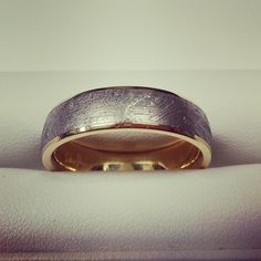 Meteorite wedding band lined with yellow gold by Chris Ploof