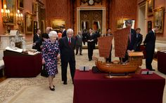 Queen Elizabeth II and the Singapore President Tony Tan Keng Yam view a display…