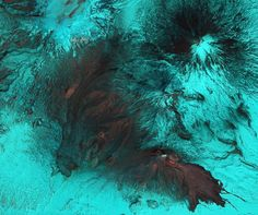 """Russia's Bezymianny Volcanocovers the icy landscape in ash in a false-color picture taken by a NASA satellite on April 22. The volcano starting erupting on April 14, spewing ash as high as 25,000 feet (7,600 meters).    In the image, ash and bare rock appear gray while snow and ice are tinged with blue. A red """"hot spot"""" shows where fresh lava is likely emerging from the volcano's dome, and a larger region to the southeast marks an active lava flow."""