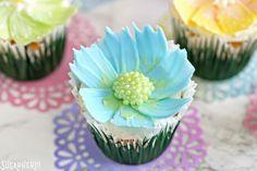 Easy Chocolate Flower Cupcakes - close-up of lemon-coconut cupcake with blue chocolate flower | From SugarHero.com