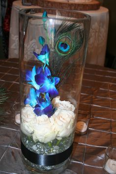 """Inexpensive centerpiece of a 15"""" tall cylinder vase with white roses at the base and blue orchids in the center.  Accented with a peacock feather!"""