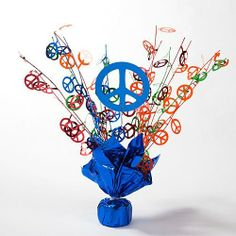 Peace Sign Sparkle Centerpiece by Shindigz. $2.99. Our Peace Sign Sparkle Centerpiece will add sparkle to your groovy party with the red, blue, green, and orange peace signs. The colorful centerpiece features a weighted bottom wrapped in blue foil and dozens of sprays covered with multi-colored peace signs. Each of the peace sign centerpieces measures 15 inches tall. Decorate your tables at your next 60's or hippy party with our fun Peace Sign Sparkle Centerpiece.