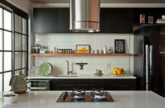 Decoração contemporânea com toque retrô e elementos industriais com ambientes integrados. Na cozinha parede de tijolinhos brancos e armário preto.