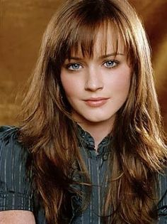 Short, shoulder length auburn hair and sparkly gray-blue eyes with freckles on her nose and pale skin.Beautiful hair color ideas for blue eyes.