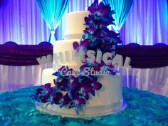 3 tier wedding cake, covered in purple and blue orchids draping down the entire cake. Accented with just a little silver bling to add some sparkle