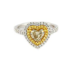 Fancy Yellow Heart Double Halo Diamond Ring A gorgeous heart shaped fancy yellow diamond takes center stage in this unique ring.  The heart shaped diamond center is accented by a halo of fancy yellow round brilliant diamonds and another halo of white diamonds, with diamond accents in the band as well.  14 karat white and yellow gold.   1.55 ctw