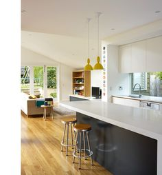 Modern grey/white kitchen with yellow lights and window splashback