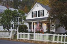 White clapboard house with a white front picket fence