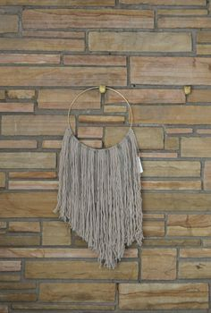 """Unique - One of a Kind Wool + Gray Leather Natural Fiber Macrame Wall Hanging on 12"""" Brass Hoop. Wool fibers mixed with gray leather fringe strips - by Astral Riles  Size: Large Materials: 100% wool + 100% genuine leather  Dimensions: 13""""w x 23""""w"""