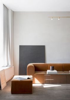 A minimal tan sofa in a clean, open plan lounge space. This is in Kinfolk magazine's gallery and office space in Copenhagen.