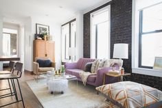 Lo Bosworth's NYC apartment in Nolita - purple couch in living room, black wall