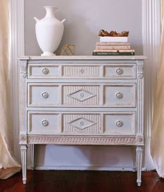 The Aria Collection is inspired by the Swedish Gustavian style. The Three Drawer Dresser features hand carving, delicately fluted legs, and a timeworn patina.