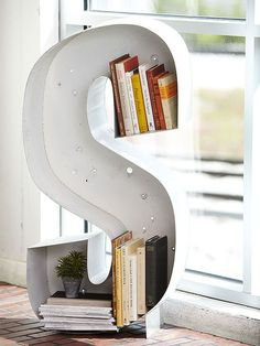Talk about a smart storage solution: a salvaged sign letter gets a second life as a shapely holder for books and small plants.