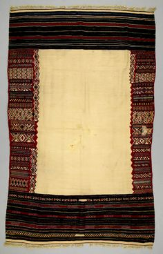 Africa | Shawl from the Berber people living in the Kabylie region of Algeria | ca. 1890 - 1930 | Wool | The Kabyle Berbers of the Kabylie region of northern Algeria wove fine women's shawls using the interlocking-tapestry technique. The shawls were woven very densely from the finest sheep wool. The undecorated, white central field, combined with asymmetrical border patterns, resulted in a dynamic composition unique to weavings from this area.