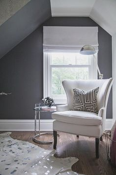Chic bedroom features a reading corner which sits under a sloped ceiling boasting a white wingback ...