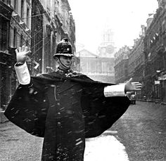 Caped crusader: with his helmet lightly covered with snow, a police constable directs traffic on a practically deserted Ludgate Hill in February 1962. Aubrey Hart