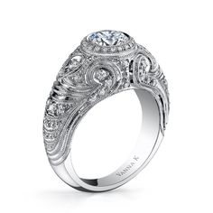 VannaK.com  Diamond: Round 0.41 carats; (not including 1 Carat Bezel Set center stone)  Hand-Engraved by expert artisans for the perfect profile combiningwhite hand-selected diamonds to maximize the sparkle from the center stone. The Hand-Engraved collection was created to last a lifetime and beyond.