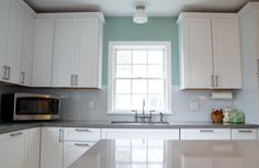 The painted white cabinets & white glass backsplash greatly contribute to the brightness of this Minneapolis kitchen.
