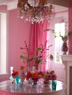 Pink dining room - pretty chandelier - love the glass vase collection on the table