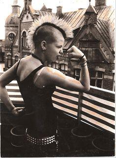 Female punk showing her guns,  mohawk, rooftops