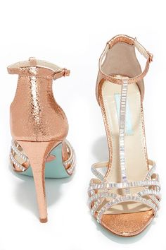 "What better way to standout and shine than in the Blue by Betsey Johnson Ruby Rose Gold Rhinestone Heels! These breathtaking dress sandals have a crackly metallic peep-toe upper with satin straps topped in glimmering rhinestones. Adjustable ankle strap. 4.25"" wrapped stiletto heel. Cushioned insole. Felted rubber sole. Available in whole and half sizes. Measurements are for a size 6. All man made materials."
