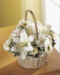 A radiant basket in white.  An Asiatic lily, Matsumoto asters, white alstroemeria, and, mini carnations nestle with baby's breath in a handled basket .  A sweet arrangement well-suited to send to the residence as well as the funeral home. Divinity Basket of Flowers - $74.97 Available online for worldwide delivery at Brant Florist.