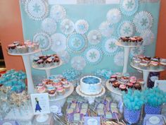 The dessert table was further complimented with a stunning backdrop featuring custom Frozen inspired paper rosettes by Quilted Cupcake (Etsy).  Table included Frozen themed dessert pops from Lauren Walleart; blue, white and lavender candy by Oh Nuts!; cupcakes with Frozen cupcake toppers by DsCustom Toppers (Etsy).  Labels by Custom Event Creations (Etsy) and Favor Bags by The SHOP by Petite Party Studio (Etsy)