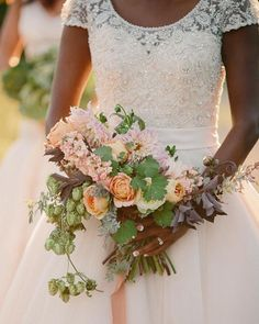Peach-colored cafe au lait dahlias and garden roses, combined with stock, foliage, and fresh hops make a perfectly rustic-chic arrangement | Brides.com