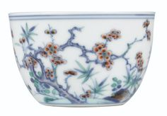 A FINE DOUCAI 'MAGPIES AND PRUNUS' CUP MARK AND PERIOD OF YONGZHENG Finely potted with curved sides rising from a countersunk base, the exterior delicately enamelled with a continuous scene depicting a magpie in flight, its head turned sharply to its mate on the ground, together with leafy stems and a long gnarled branch bearing prunus buds and blossoms, the base inscribed in underglaze-blue with a six-character reign mark within a double-circle 6.9 cm