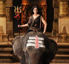 Indian actress Anushka Shetty riding bareback on an elephant in Bahubali movie.