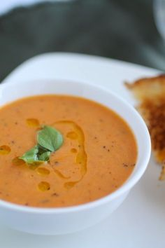 Vegan Roasted Tomato Soup #food #recipes 8 roma tomatoes, halved 5 sprigs thyme 2 bay leaves 3 cloves garlic, peeled 3 Tbsp. + 2 Tbsp. extra virgin olive oil salt and pepper to taste 1/2 of a yellow onion, roughly chopped 3 cups vegetable stock 1 cup coconut milk 2 tsp. tomato paste pinch of paprika 1/2 tsp. lemon zest 1/2 tsp. dried basil extra olive oil and fresh basil, for garnish