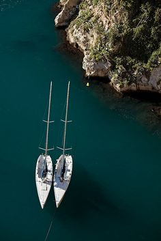 Two yachts anchored next to cliff