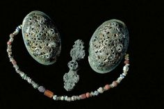 Viking grave find , glass beads hung between two tortoise brooches.