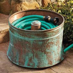 Clever.... A washing machine tub... good use for water hose storage. I just happen to have my last washers tub, I better get it out so it can get some rust going on!!