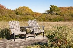 """""""Two Adirondack chairs sit on a simple deck against the beginnings of fall foliage."""""""