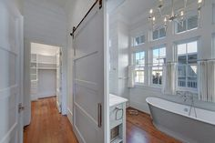 A gray barn door on rails opens to a gray bathroom fitted with a polished nickel 8 light chandelier hung in front of a cast iron freestanding tub finished with a polished nickel tub filler positioned under a wall of windows dressed in white linen cafe curtains and framed by gray shiplap trim.