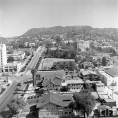 Nowadays, the northern end of Vine Street in Hollywood is largely offices and parking lots. But in this aerial view circa early 1940s, we can see that the neighborhood was once largely residential, with large and lovely homes and scattered with trees. It's also nice to see the area before it was bisected by the Hollywood Freeway. And in those pre-smog days, we can clearly see Mt. Lee and the Hollywoodland sign.