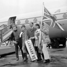 Lord John (centre), owner of a Carnaby Street boutique, pictured at Heathrow Airport before heading to Milan and Florence to promote Carnaby Street fashions. His companions are (l-r) Harold Gold, Jackie Denton, Liz Gold and Jeffrey. Lord John, Swinging London, Carnaby Street, Heathrow Airport, National Photography, London England, About Uk, Florence, Signage