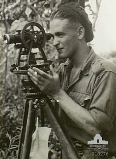 Tsimba area, Bougainville. 21 March 1945. Bombardier Doug Bundy of Melbourne, Vic, and of Artillery Regiment, looking through a theodolite surveying the area.