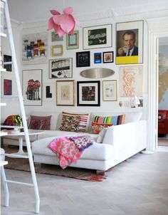 Gallery wall, lovely white couch and worn in rug. :) Plus splashes of pink!