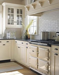 Fresh Farmhouse THE CREAMY IVORY PAINTED CABINETS AND THE DARK ACCENTS , AND THE SHINY SUBWAY TILES . SO CLEAN AND FRESH