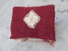Dos du livret - application d'un détail de broderie sur du feutre nuno laine et tissu lamé découpé sous la dentelle