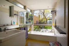 Ein traditionelles Bad, das hat eine tiefe Badewanne, Waschbecken aus Marmor, weiße Fliesen und Licht braun Bodenbelag. / Foto von Paul Welschmeyer Architekten & Energie Berater
