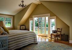 Maine Oceanfront cottage master bedroom with balcony; cathedral ceiling; vintage chandelier; gable end balcony;