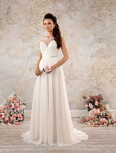 A full length, lace modern vintage wedding dress with sheer yoke, sweetheart neckline, shirred A-line skirt, and chapel train.
