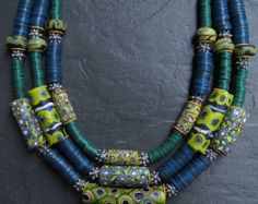 A large old Himalayan clear glass bead which I found in Nepal takes focal point in this gorgeous necklace. It is surrounded by six antique Bohemian glass trade beads from the late 1800s. A couple of small chips in the beads only add more charm and a testament to their journey in the African trade. There are nine antique rare light green Vaseline trade beads from the early 1900s with contemporary Lapis rondelles, Bali sterling silver beads caps, chain and clasp. The two silver bells on…